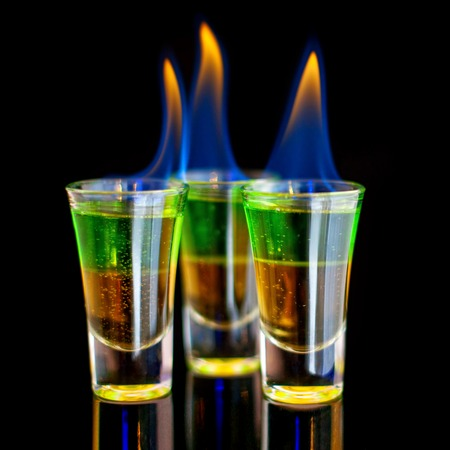 Burning Green cocktail in shot glass on black background.