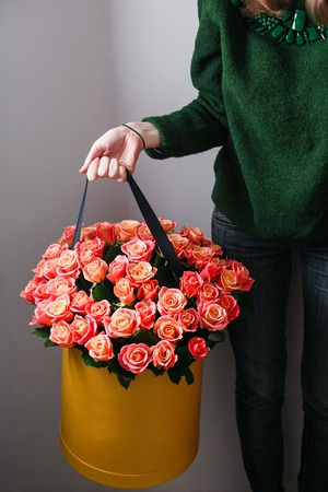 plastered wall: Nice young blonde girl with Blue Eyes and healthy Long Blond Hair smelling flowers holding red roses bouquet in hat box against the plastered wall, wearing jeans and knit sweater.