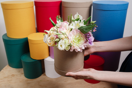 plastered wall: Work florist, bouquet in a round box. smelling flowers holding peach roses bouquet in hat box against the plastered wall.