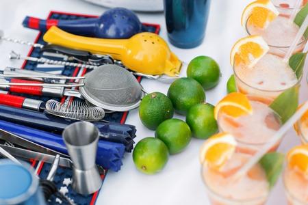 Complete cocktail set for bartender in blue. ime green and orange cocktails.