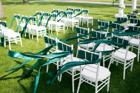 wedding chairs: White wedding chairs with green ribbon outdoors