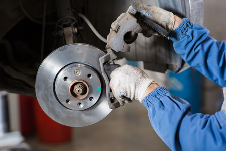 Brand new brake disc on car in a garage. Auto mechanic repairing a car. Archivio Fotografico