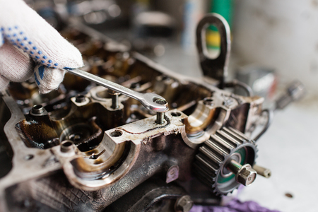 cam gear: Mechanic hands tighten nut with wrench while repairing engine.