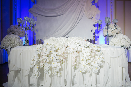 Beautiful restaurant interior table decoration for wedding. Flower . White orchids in vases. luxury candleholders. Stock Photo