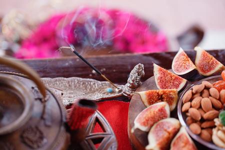 fumer l'encens. Figues et noix de petit déjeuner indien sur une table en bois. Nature morte avec du thé vert fumant chaud.