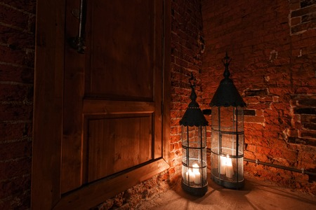room door: wooden door in brick room with candles. Winter Is Coming.