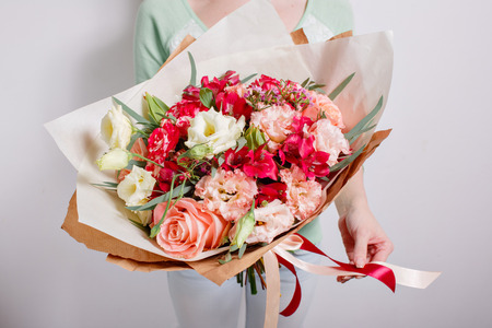 Rich bunch of pink eustoma and roses flowers, green leaf in hand Fresh spring bouquet. Summer Background
