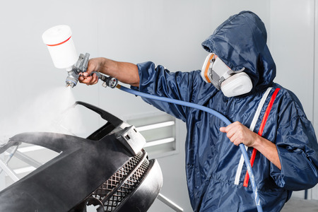 protective: worker painting a car black blank parts in special garage, wearing costume and protective gear. Stock Photo