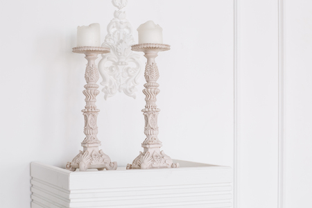 stucco: White antique candlesticks with candles close up. stucco wall.