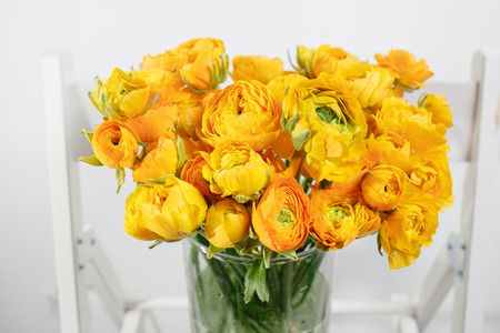 beautiful bouquet buttercup in a glass vase on a white background. colorful color mix flower.