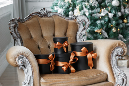 Wrapped gift black boxes with ribbons as Christmas presents on a chair.