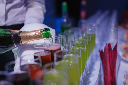 popping the cork: Champaign. being pored into glasses. banquet table. blue light Stock Photo