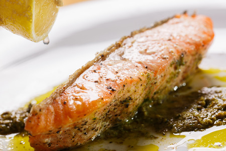 Crisp Salmon Steak with pesto Sauce to top drop lemon. Stock Photo