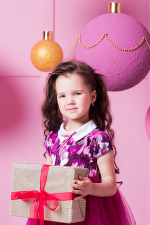 Brunette girl child 5 years old in a pink dress. in holiday rose quartz room with gifts Stock Photo