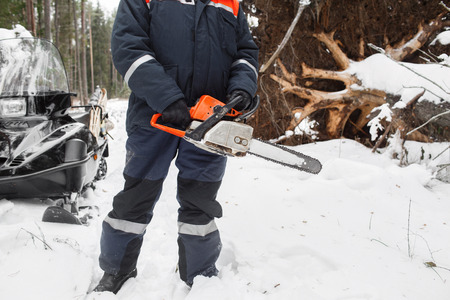 proffesional occupation: Proffesional Lumberjack hold hand saw. Winter wearing protection clothes using chainsaw. clean fallen trees. Stock Photo