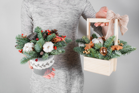 adorning: young woman holding christmas compositionin hands in light, seasonal holidays, rustic theme, adorning.