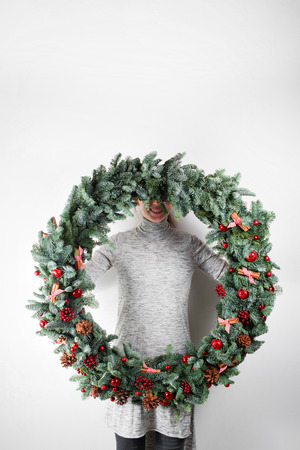adorning: young woman holding christmas large wreath in hands in light, seasonal holidays, rustic theme, adorning.