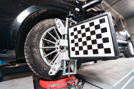 Car on stand with sensors on wheels for wheels alignment camber check in workshop of Service station.