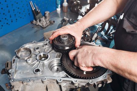 Dwarsdoorsnede van een auto-versnellingsbak. monteurs werk in de garage. de hand automonteur in werkkleding. Stockfoto - 67027593