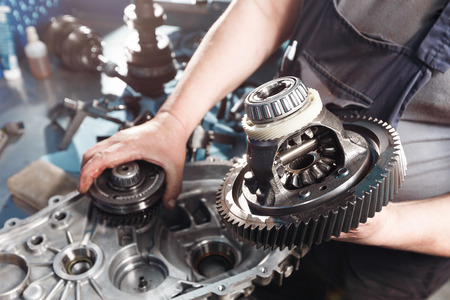 Cross-section of a car gearbox. mechanics work in the garage. hand car mechanic in working clothes. Standard-Bild
