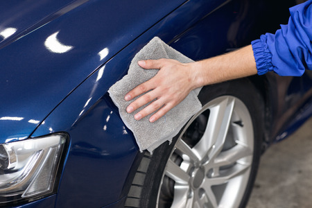 valeting: A man polishing cleaning car with microfiber cloth, car detailing or valeting concept