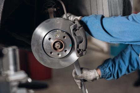 Brand new brake disc on car in a garage. Auto mechanic repairing a car. Stockfoto