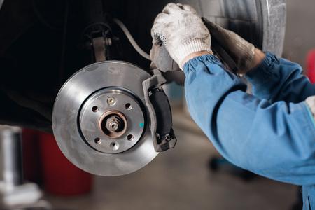 Brand new brake disc on car in a garage. Auto mechanic repairing a car. Standard-Bild