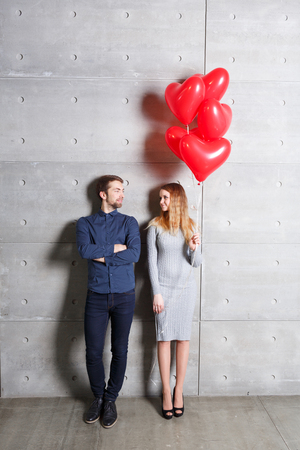 flying kiss: Valentines day concept. Loving couple with red heart balloons on gray background