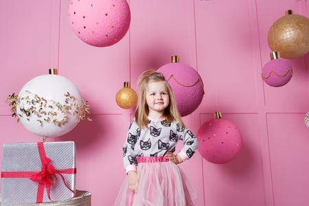 Pretty girl child 4 years old in a blue dress. Baby in Rose quartz room decorated holiday Stock Photo