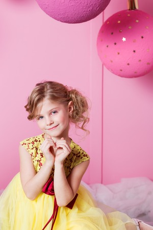 Valentine heart to make your fingers. Pretty girl child 6 years old in a yellow dress. Baby in Rose quartz room decorated holiday