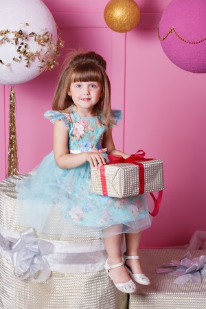 Pretty girl child 4 years old in a blue dress. Baby holding a gift in their hands. Rose quartz room decorated holiday.