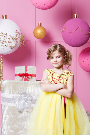 Pretty girl child 6 years old in a yellow dress. Baby in Rose quartz room decorated holiday Stock Photo