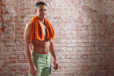 Athlete after a workout with  towel on old red bricks background
