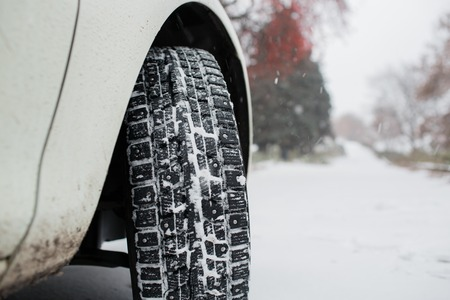 night shift: Closeup of car tires in winter. the first snow in late autumn