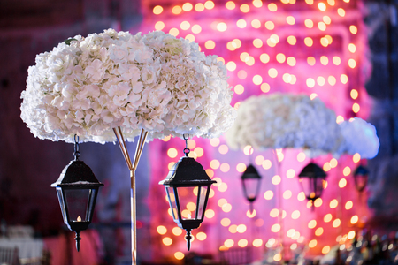 Lights and lanterns in the night. Bokeh Wedding Banquet. The chairs and round table for guests. Stock Photo