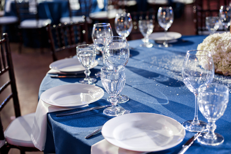 Wedding. Banquet. The chairs and round table for guests, served with cutlery and crockery and covered with a blue tablecloth. Stock Photo