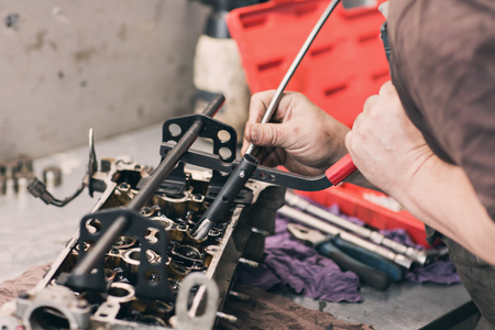 carburetor: Car mechanic in garage with old car engine piston And valve Stock Photo