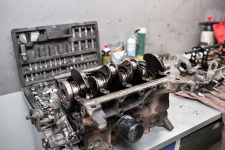 gudgeon: Engine crankshaft, valve cover, pistons. mechanic repairman at automobile car engine maintenance repair work