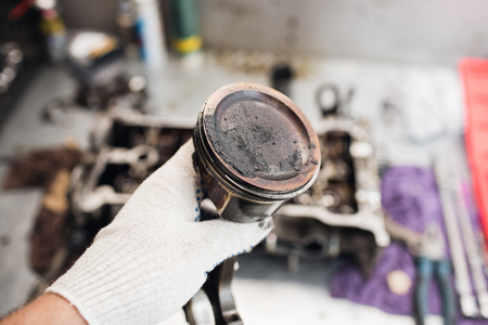 carburetor: Car mechanic in garage with old car engine piston.