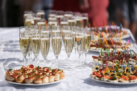glasses with champagne. catering banquet table. a lot of snacks and canapes