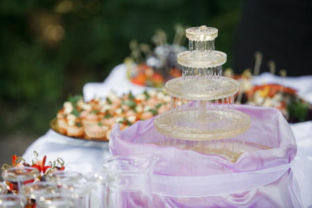Fountain with champagne, glasses. catering banquet table. a lot of snacks and canapes