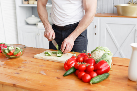 throwing knife: Middle-aged athlete, cuts vegetables salad of cucumber and tomato. Vegetarian food Stock Photo