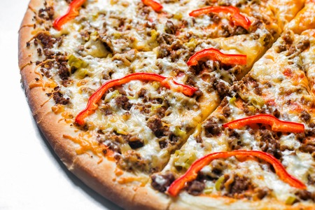 pizza with minced meat and peppers, by cut to pieces on a metal table. selective focus on the filling close-up.