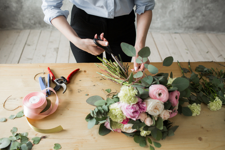 Florist at work: pretty young woman making fashion modern bouquet of different flowers