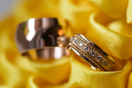 diamond ring on yellow flower. wedding rings together. selective focus