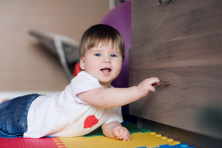 the child 1 year old opens the drawers or closet . Happy baby boy lies on floor at childrens room and playing. Stock Photo