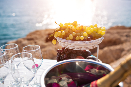 buffet table fruit and wine. wedding in cyprus, bride and groom on a stone bridge in Agia Napa. The view of the sea. On the rock coast. Stock Photo