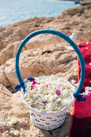 basket closeup with petals. wedding in cyprus, bride and groom on a stone bridge in Agia Napa. arch and table for registration of marriage. The view of the sea. On the rock coast
