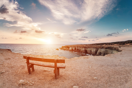 about you: sunset in Cyprus - Mediterranean Sea coast. Sea Caves near Ayia Napa. the bench in the background of space. you can sit and think about life.