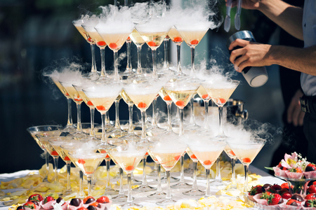 Champagne pyramid on event, party or banquet. cherry in the glass. Dry ice floats